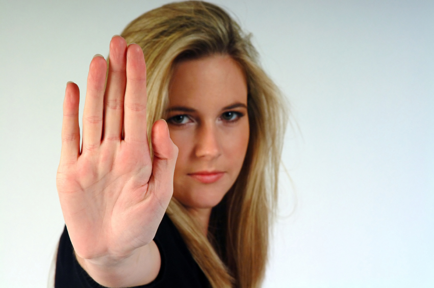 Young woman making a stop gesture, palm outwards.